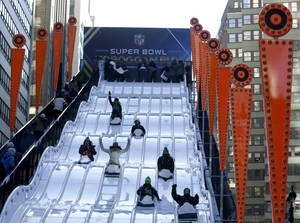 Photo - People make their way down the toboggan slide during Super Bowl Boulevard festivities Wednesday, Jan. 29, 2014, in New York. The Seattle Seahawks are scheduled to play the Denver Broncos in the NFL Super Bowl XLVIII football game on Sunday, Feb. 2, in East Rutherford, N.J. (AP Photo/Julio Cortez)