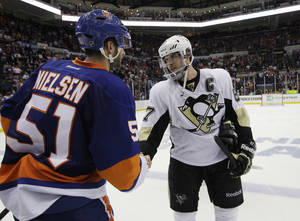 Photo - New York Islanders center Frans Nielsen (51), of Denmark, congratulates Pittsburgh Penguins center Sidney Crosby (87) after the Penguins defeated the Islanders in overtime of Game 6 of a first-round NHL Stanley Cup playoff hockey series in Uniondale, N.Y., Saturday, May 11, 2013.  The top-seeded Penguins advanced to the Eastern Conference semifinals with a 4-3 win. (AP Photo/Kathy Willens)