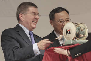 Photo - Thomas Bach, left, president of the IOC beats a Korean traditional drum as Hwang Chang-gyu, chairman of KT, smiles after the signing of a partnership between Pyeongchang's organizing committee and KT in Seoul, South Korea, Tuesday, July 1, 2014. Under their partnership, KT will provide high-speed Internet service throughout the competition using up-to-date technology and will help Pyeongchang host the most advanced Olympic Games in terms of information and communication technology. (AP Photo/Ahn Young-joon)