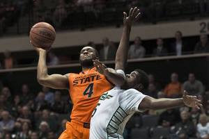 Photo - Oklahoma State's Brian Williams (4) goes up for a shot under pressure from South Florida's John Egbunu, right, during the first half of an NCAA college basketball game Monday, Nov. 25, 2013, in Tampa, Fla. (AP Photo/Steve Nesius)