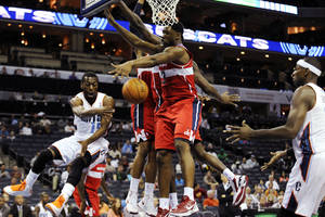 Photo -   Charlotte Bobcats guard Kemba Walker (15) passes around Washington Wizards forward Kevin Seraphin (13) to Bobcats center Brendan Haywood (33) during the first half of an NBA preseason basketball game in Charlotte, N.C., Sunday, Oct. 7, 2012. (AP Photo/Mike McCarn)