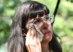 Photo - Kate Kelly wipes a tear from her face during a vigil Sunday, June 22, 2014, in Salt Lake City. While Kelly's former church leaders meet in Virginia on Sunday night to decide if she'll be ousted from her church, the founder of a prominent Mormon women's group will hold a vigil in Salt Lake City along with hundreds of her supporters.   (AP Photo/Rick Bowmer)