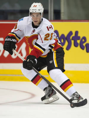 Photo - Calgary Flames forward Sean Monahan moves the puck against the New York Islanders during the third period of an NHL hockey game Tuesday, Sept. 17, 2013, in Regina, Saskatchewan. The Flames won 4-2. (AP Photo/The Canadian Press, Liam Richards)