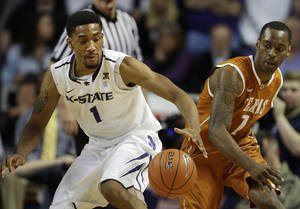 Photo - Kansas State guard Shane Southwell (1) reaches for the ball while covered by Texas guard Sheldon McClellan (1) during the first half of an NCAA college basketball game in Manhattan, Kan., Wednesday, Jan. 30, 2013. (AP Photo/Orlin Wagner)