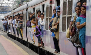 Photo - Commuters hang by doors of a crowded local train in Mumbai, India, Tuesday, July 8, 2014. India's new rail minister Sadananda Gowda on Tuesday proposed allowing foreign investment to modernize the country's cash-strapped state railways. India has one of the world's largest railways, which transports 23 million passengers a day. Indian Railways is one of the world's biggest employers with more than 1.3 million employees. The network lost 300 billion rupees ($5 billion) last year. (AP Photo/Rajanish Kakade)