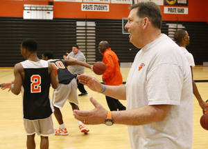 photo - Putnam City head coach A.D. Burtschi smiles and claps at the end of the final basketball practice before the state tournament for the Putnam City Pirates boys basketball team at Putnam City High School in Warr Acres, Okla., Wednesday, March 6, 2013. Photo by Nate Billings, The Oklahoman