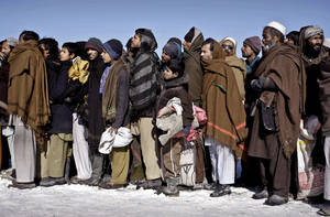 photo - Internally displaced Afghans wait in line to receive firewood donated by Welt Hunger Hilfe 'German Agro Action' in Kabul, Afghanistan, Sunday, Dec. 30, 2012.  Around 240 internally displaced families received firewood. (AP Photo/Musadeq Sadeq)