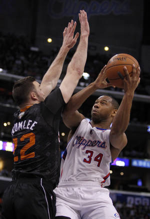 Photo - Los Angeles Clippers guard Willie Green (34) shoots over Phoenix Suns center Miles Plumlee (22) during the first half of an NBA basketball game Monday, March 10, 2014, in Los Angeles. (AP Photo/Alex Gallardo)