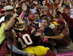 Photo -   Washington Redskins quarterback Robert Griffin III (10) celebrates with the fans after a 76-yard touchdown run during the second half of an NFL football game against the Minnesota Vikings, Sunday, Oct. 14, 2012, in Landover, Md. (AP Photo/Pablo Martinez Monsivais)
