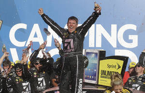 Photo - Sprint Cup Series driver Jamie McMurray celebrates after winning the NASCAR Sprint Cup Series auto race at the Talladega Superspeedway in Talladega, Ala., Sunday, Oct. 20, 2013.(AP Photo/Jay Sailors)