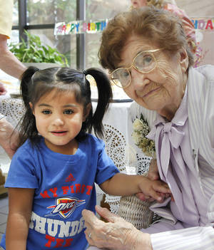 photo - Mercy Tasi, 2, poses for a photo with Sister Mary Clotilda Toelle during the nun's 100th birthday celebration Wednesday at The Mercy Convent next to Mercy Hospital Oklahoma City. Mercy's mom named her after the hospital.   Photos By David McDaniel, The Oklahoman
