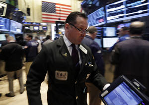 Photo - FILE - In this April 30, 2014 photo, trader Edward Curran rushes across the New York Stock Exchange floor. (AP Photo/Richard Drew, File)