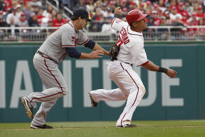 Photo - Washington Nationals shortstop Ian Desmond (20) is caught by Atlanta Braves starting pitcher David Hale (57) in a run down between third and second base during the fifth inning of a baseball home opener at Nationals Park Friday, April 4, 2014, in Washington. (AP Photo/Alex Brandon)
