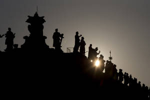 Photo - The sun sets behind the statues on top of the Bernini colonnade in St. Peter Square, at the Vatican, Monday, March 4, 2013. Cardinals from around the world have gathered inside the Vatican for their first round of meetings before the conclave to elect the next pope, amid scandals inside and out of the Vatican and the continued reverberations of Benedict XVI's decision to retire. (AP Photo/Andrew Medichini)