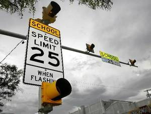 photo - Workers from Traffic Signals. Inc. remove old signs after new signs were erected at various  school   zone locations around Oklahoma City. Sign at left will be removed when electrical connection is removed. Newer sign that hangs above the street is in background. This location is at NW 18 and Classen. Photo by Jim Beckel, The  Oklahoman