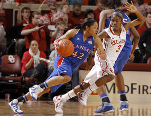 Photo - Kansas' Natalie Knight (42) dribbles up court as Oklahoma's Aaryn Ellenberg (3) defends during the women's college basketball game between the Oklahoma Sooners and the Kansas Jayhawks at the LLoyd Noble Center in Norman, Okla., Sunday, March, 4, 2011. Photo by Sarah Phipps, The Oklahoman