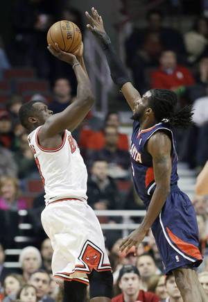 Photo - Chicago Bulls forward Luol Deng, left, shoots over Atlanta Hawks forward DeMarre Carroll during the first half of an NBA basketball game in Chicago on Saturday, Jan. 4, 2014. (AP Photo/Nam Y. Huh)