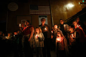 Photo - People hold candles during a vigil at the Darrington Community Center on Saturday, April 5, 2014. The vigil was held on the two week anniversary of the Oso mudslide and brought together hundreds of local residents affected by the disaster. (AP Photo/seattlepi.com, Joshua Trujillo)