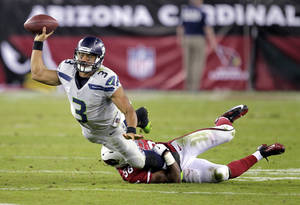 Photo - Seattle Seahawks quarterback Russell Wilson (3) gets a pass off as Arizona Cardinals inside linebacker Karlos Dansby (56) brings him down during the second half of an NFL football game, Thursday, Oct. 17, 2013, in Glendale, Ariz. (AP Photo/Rick Scuteri)