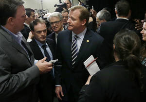 photo -   NFL football commissioner Roger Goodell is surrounded by reporters after delivering a Dean's Distinguished Lecture at Harvard School of Public Health in Boston, Thursday, Nov. 15, 2012, where he discussed some of the rules that have been created to limit concussions in the game of football. Goodell said the league will do what it needs to do to protect the safety of its 1,800 players. (AP Photo/Elise Amendola)