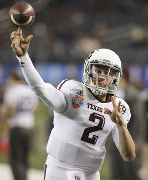 photo - Texas A&M quarterback Johnny Manziel warms up before the Cotton Bowl NCAA college football game against Oklahoma at Cowboys Stadium on Friday, Jan. 4, 2013, in Irving, Texas. (AP Photo/LM Otero)