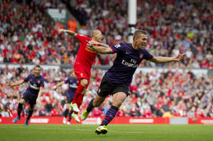 Photo -   Arsenal's Lukas Podolski, right, celebrates after scoring against Liverpool during their English Premier League soccer match at Anfield Stadium, Liverpool, England, Sunday, Sept. 2, 2012. (AP Photo/Jon Super)