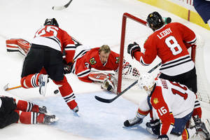 Photo - Chicago Blackhawks goalie Antti Raanta (31) loses his helmet on a play during the third period of an NHL hockey game against the Florida Panthers on Sunday, Dec. 8, 2013, in Chicago, Ill. (AP Photo/Andrew A. Nelles)