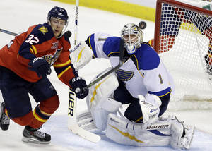 Photo - St. Louis Blues goalie Brian Elliott (1) and Florida Panthers right wing Kris Versteeg watch the puck during the second period of an NHL hockey game Friday, Nov. 1, 2013, in Sunrise, Fla. (AP Photo/Lynne Sladky)