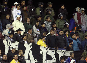 photo - Police officers stand guard next to Brazil's Corinthians' fans during a Copa Libertadores soccer match against Bolivia's San Jose in Oruro, Bolivia, Wednesday, Feb. 20, 2013. During the match, a fourteen-year-old young man died after being injured allegedly by a bomb sound, police said. (AP Photo/Juan Karita)