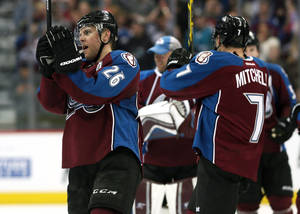 Photo - Colorado Avalanche center Paul Stastny, left, joins center John Mitchell in celebrating after the Avalanche's 3-2 victory over the San Jose Sharks in an NHL hockey game in Denver on Saturday, March 29, 2014. The win secures the Avalanche will make their first appearance in the NHL Playoffs since 2010. (AP Photo/David Zalubowski)