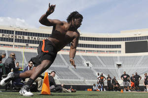 photo - OSU's Nigel Nicholas rounds a cone as part of an agility exercise during Pro Day at Boone Pickens Stadium on the campus of Oklahoma State University in Stillwater, OK, Tuesday, March 12, 2013,  By Paul Hellstern, The Oklahoman