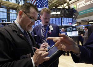 photo - In this Monday, Feb. 25, 2013, photo, Trader Edward Curran, left, works on the floor of the New York Stock Exchange. Uncertainty over the outcome of a budget battle in Washington pushed world stock markets lower on Monday March 4, 2013. (AP Photo/Richard Drew)