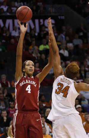 Photo - Oklahoma center Nicole Griffin (4) shoots over Texas center Imani McGee-Stafford (34) during the first half of an NCAA college basketball game in the quarterfinals of the Big 12 Conference women's tournament in Oklahoma City, Saturday, March 8, 2014. (AP Photo/Sue Ogrocki)