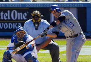 Photo - Colorado Rockies' Michael Cuddyer hits a single as Los Angeles Dodgers catcher A.J. Ellis and home plate umpire Bob Davidson watch during the fifth inning of a baseball game, Sunday, Sept. 29, 2013, in Los Angeles. The Rockies won 2-1. (AP Photo/Mark J. Terrill)