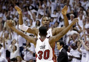 Photo - Miami Heat's Chris Bosh and Norris Cole (30) celebrate after the Heat defeated the Chicago Bulls 94-91 in Game 5 of an NBA basketball Eastern Conference semifinal, Wednesday, May 15, 2013, in Miami. The win sent the Heat to the conference finals. (AP Photo/Wilfredo Lee)