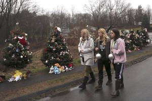 Photo - FILE - In this Monday, Dec. 17, 2012 file photo, mourners carry ornaments to decorate the Christmas trees at one of the makeshift memorials for the Sandy Hook Elementary School shooting victims, in Newtown, Conn. In the wake of the shooting, the grieving town is trying to find meaning in Christmas. (AP Photo/Mary Altaffer, File)