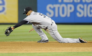 Photo - Chicago White Sox second baseman Marcus Semien (5) makes a diving stop in the seventh inning of a baseball game against the Texas Rangers, Saturday, April 19, 2014, in Arlington, Texas. The Texas Rangers won 6-3. (AP Photo/Matt Strasen)