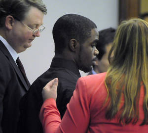 "Photo - De'Marquise Elkins, center, stands with his lawyers, public defender Kevin Gough and assistant public defender Elizabeth Ashley Wood, as he is sentenced, Thursday, Sept. 12, 2013 in Brunswick, Ga. Elkins convicted of fatally shooting a baby in a stroller was sentenced Thursday to spend the rest of his life in prison with no chance of parole after the grieving mother asked a judge to punish the gunman for taking ""the love of my life."" (AP Photo/The Brunswick News/Bobby Haven)"