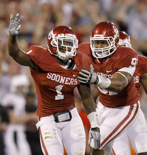 Photo - Oklahoma's Tony Jefferson (1) celebrates with Oklahoma's R.J. Washington (91) after his third interception during the college football game between the University of Oklahoma Sooners (OU) and the Ball State Cardinals at Gaylord Family-Oklahoma Memorial Stadium on Saturday, Oct. 01, 2011, in Norman, Okla. Photo by Bryan Terry, The Oklahoman  ORG XMIT: KOD