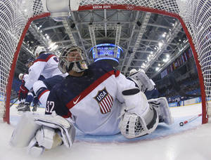 Photo - USA goaltender Jonathan Quick slides headfirst in to the goal while defending against Slovakia during the second period of the men's ice hockey game at the 2014 Winter Olympics, Thursday, Feb. 13, 2014, in Sochi, Russia. (AP Photo/Martin Rose, Pool)