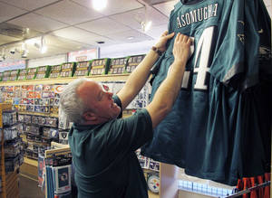 photo - Andy Hageman, owner of the House of Football in Albuquerque, N.M., shows Thursday why the authentic NFL jerseys in his store can be compared to fakes by comparing the jerseys' quality. He said that authentic NFL jerseys do not have cardboard behind the numbers. AP Photo <strong>Russell Contreras</strong>