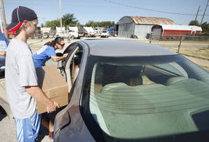 photo - Volunteer Jake Conder, 13yr. loads a car during a joint food drive with Feed The Children and Mustard Seed Development Corporation   in Oklahoma City, Tuesday 25, 2012. Photo By Steve Gooch, The Oklahoman