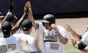 Photo - Vanderbilt's Conrad Gregor (55) is congratulated by teammates after scoring on a throwing error by South Carolina pitcher Jordan Montgomery in the second inning of a Southeastern Conference tournament college baseball game at the Hoover Met in Hoover, Ala., Thursday, May 23, 2013. (AP Photo/Dave Martin)