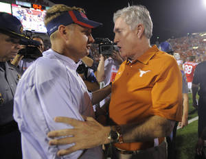 Photo -   Mississippi coach Hugh Freeze (left) and Texas coach Mack Brown (right) shake hands after their NCAA college football game in Oxford, Miss., Saturday, Sept. 15, 2012. No. 14 Texas won 66-31. (AP Photo/Austin McAfee)
