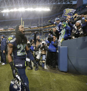 Photo - Seattle Seahawks cornerback Richard Sherman celebrates after an NFC divisional playoff NFL football game against the New Orleans Saints in Seattle, Saturday, Jan. 11, 2014. The Seahawks won 23-15. (AP Photo/Elaine Thompson)