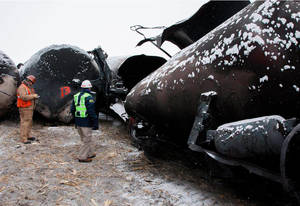 Photo - In an undated image provided by the National Transportation Safety Board NTSB board membger Robert Sumwalt, right, views damaged rail cars in Casselton, N.D.   A BNSF Railway train derailed Monday afternoon, Dec. 30, 2013,  near the eastern North Dakota town of Casselton.  (AP Photo/NTSB)