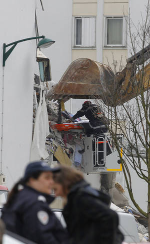 "Photo - French firemen remove the body of an unidentified victim from a building hit by an explosion that caused the collapse of its inside floors, in Reims, eastern France, Sunday, April 28, 2013.  Five people was killed and ten others injured, according to firefighters, and Reims mayor Adeline Hazan said it awas ""a very powerful explosion"" and the blast had the earmarks of a possible domestic gas explosion. (AP Photo/Jacques Brinon)"