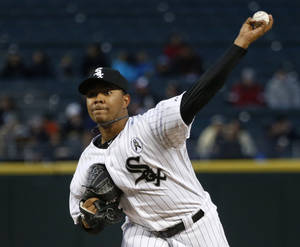Photo - Chicago White Sox starting pitcher Jose Quintana delivers during the first inning of a baseball game against the Seattle Mariners, Friday, April 5, 2013, in Chicago. (AP Photo/Charles Rex Arbogast)