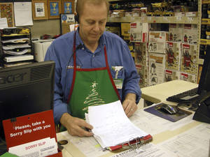 photo - Larry Boutilier, hardware manager, who has been with the Minot, N.D. Menards since 1996, looks over paperwork at the storey in Thursday, Nov. 29, 2012. The home improvement retailer says it will hire workers from its home base in Wisconsin and fly them to North Dakota to staff a store in Minot, which is near the state&#039;s booming oil patch and has more jobs than takers. (AP Photo/The Minot Daily News, Jesse D. Watson)