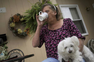 photo -   CORRECTS TYPE OF MENINGITIS TO FUNGAL INSTEAD OF BACTERIAL - Patsy Bivins, 68 of Sturgis, Ky., drinks coffee while sitting on her porch with her dog Little Britches at her apartment in Sturgis, Ky., Friday, October 5, 2012. Bivins was injected with steroids at St. Mary Sugricare in Evansville, Ind., who notified her of possibly being infected with fungal Meningitis. (AP Photo/Stephen Lance Dennee)
